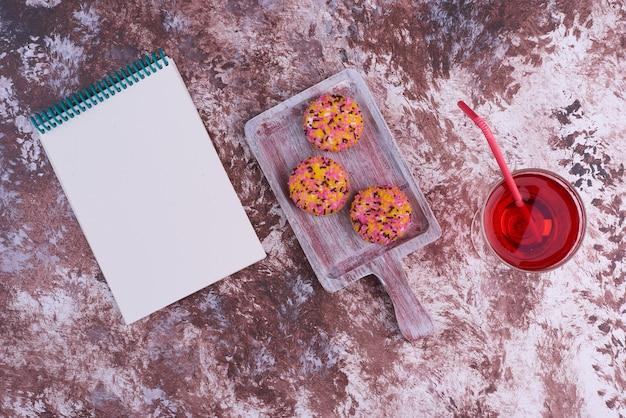 Marshmallow bladerdeegkoekjes met een glas drank en een notitieboekje opzij.