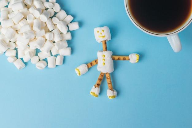 Marshmallow, een man en een kopje koffie. een collage van snoepjes. plat leggen.