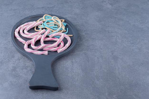 Marshmallow kleurrijke gedraaide regenboog touwen in een pan op marmeren tafel.