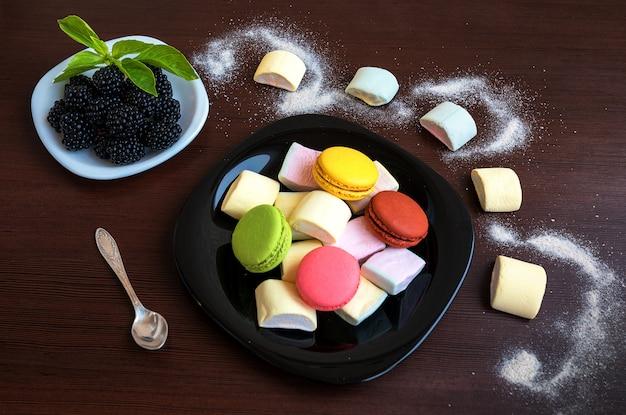 Marshmallow, macarons en suikerpoeder met cacao op een houten tafel