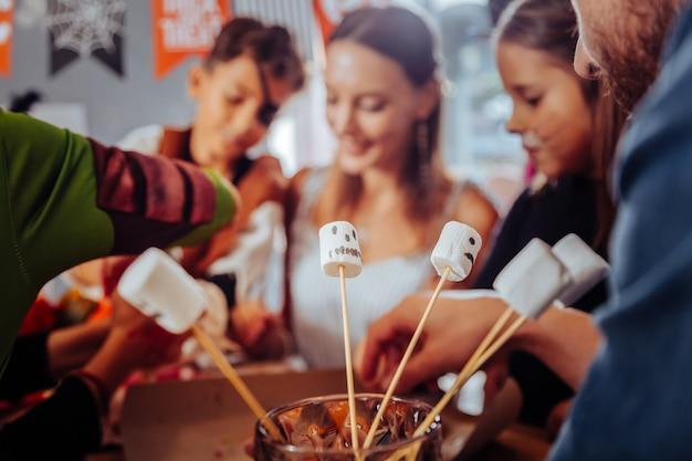 Marshmallow met gezichten. close up van marshmallows op houten stokken met grappige gezichten ter viering van halloween
