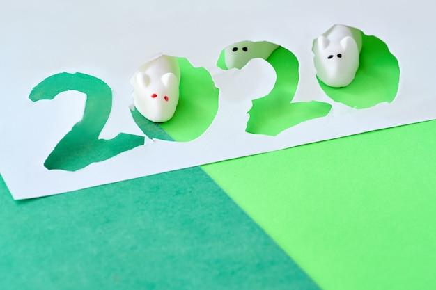 Marshmallow-muizen kijken door uitgesneden papier nummer 2020, gelukkig nieuwjaar van de muis!