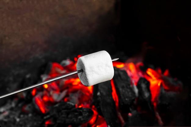 Marshmallow op een stok die boven een kampvuur wordt geroosterd. witte marshmallows koken op rode kolen in de grill. picknick in de natuur