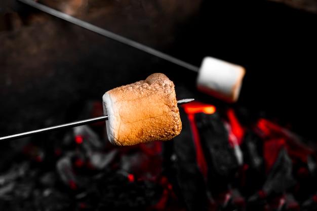 Marshmallow op een stok die boven een kampvuur wordt geroosterd