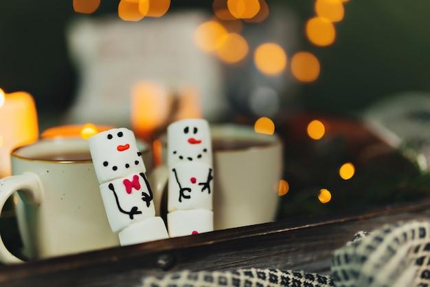 Marshmallow snowmans met kopje koffie, bokeh lichten, kerstversiering. hoge kwaliteit foto