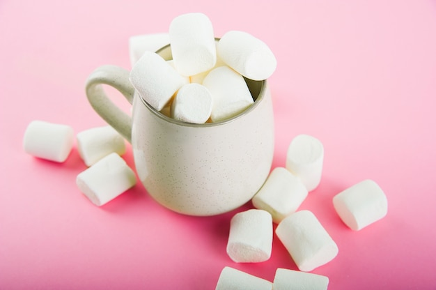 Marshmallows close-up en kopieer ruimte op een roze. marshmallows in een aardewerken mok.
