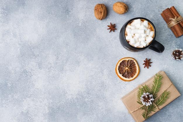 Marshmallows in een mok, cadeau specerijen en noten op grijs