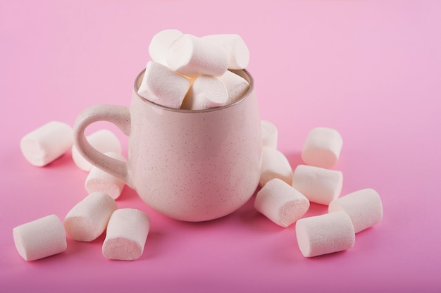 Marshmallows in een mok op een roze ruimte close-up en kopieer de ruimte. heemst in cacao of warme chocolademelk bovenaanzicht op een roze ruimte.
