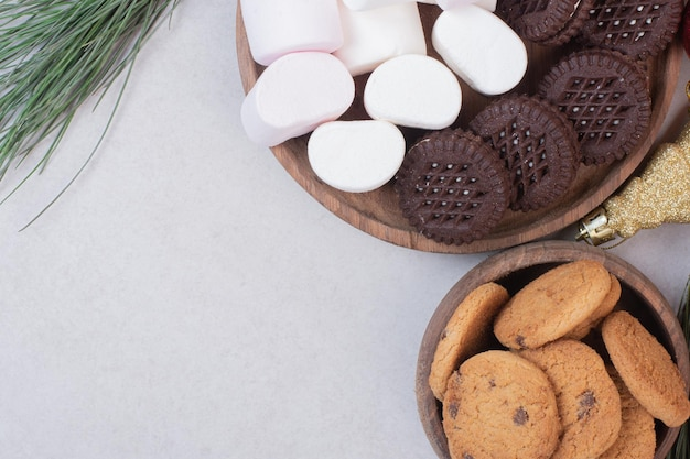 Marshmallows, koekjes op een houten bord op witte tafel.