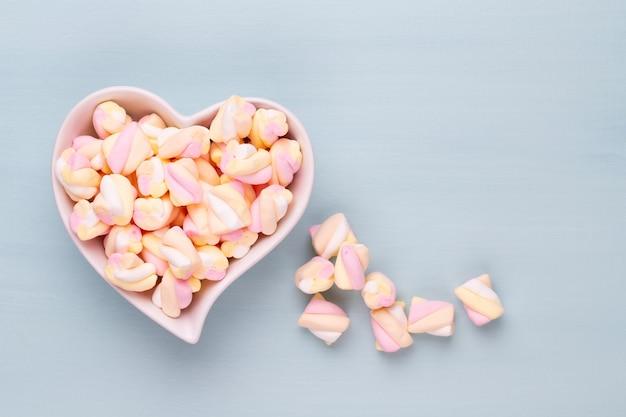 Marshmallows op blauwe achtergrond met copyspace. plat leggen of bovenaanzicht. achtergrond of textuur van kleurrijke mini marshmallows.