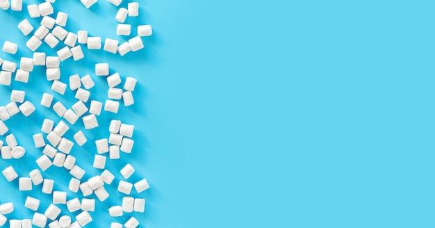 Marshmallows op blauwe achtergrond met copyspace. plat leggen of bovenaanzicht.