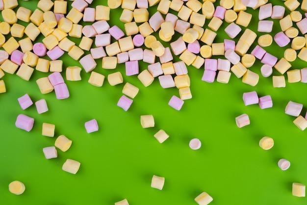Marshmallows op groene achtergrond met copyspace. plat leggen of bovenaanzicht.