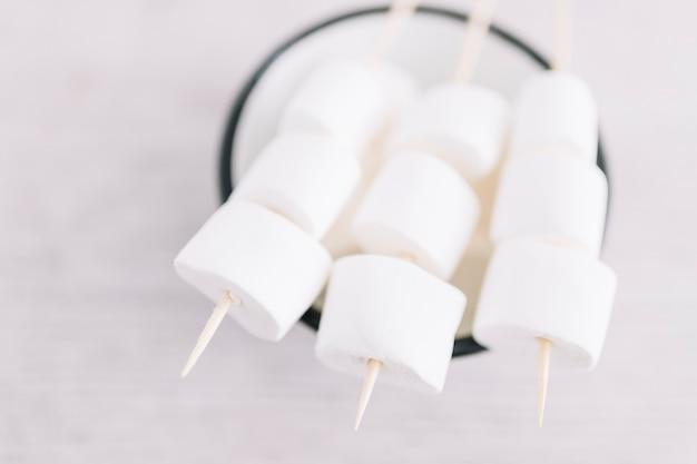 Marshmallows op stokken op beker