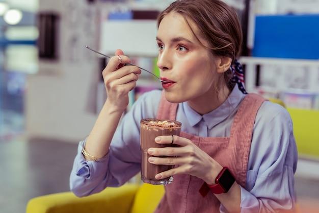Marshmallows proberen. aantrekkelijk meisje met grote grijze ogen die cacao met marshmallows proeft terwijl ze een zwaar groot glas draagt