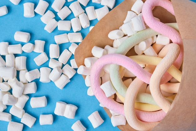 Marshmallows verpakt in papier op blauwe achtergrond