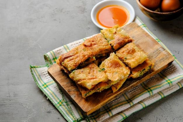 Martabak telor of martabak telur. hartig gebakken deeg gevuld met ei, vlees en kruiden. martabak telur is een van de indonesische straatvoedsel
