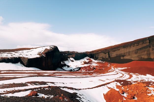 Martiaanse landschappen in ijsland. de rode krater van de seydisholar-vulkaan. de steengroeve van rode grondwinning