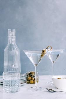 Martini-cocktail in een glas op blauwe achtergrond met olijven