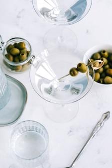 Martini-cocktail in een glas op witte achtergrond met olijven