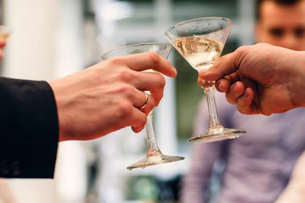 Martini-glazen in de handen van het vieren van de vakantie