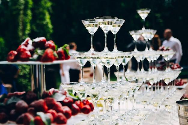 Martini glazen piramide. glazen voor sterke drank op tafel. buffettafel bedekt met een wit tafelkleed.