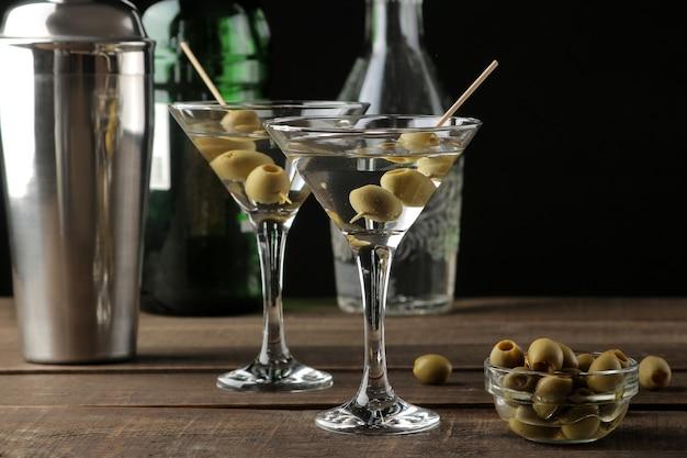 Martini in een glas wijnglas met groene olijven op een spies op een bruin houten tafel. cocktails. bar