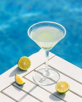 Martini met limoen rond een zwembad.