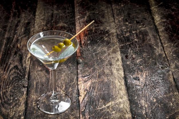 Martini met olijven. op een houten achtergrond.