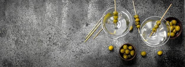 Martini met olijven. op een rustieke achtergrond.