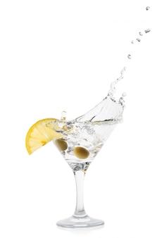 Martini splash met citroen en groene olijven in een transparante haan
