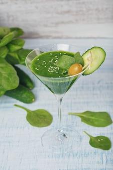 Martiniglas gevuld met verse groene spinazie en komkommer smoothie op lichtblauwe houten ondergrond. niet-alcoholische dranken. gezond eten en vegetarisch concept.