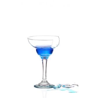 Martiniglas met blauw water en gebroken glas