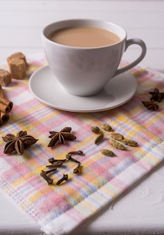Masala chai thee in cup, bruine suiker, kaneelstokjes, anijs en badian