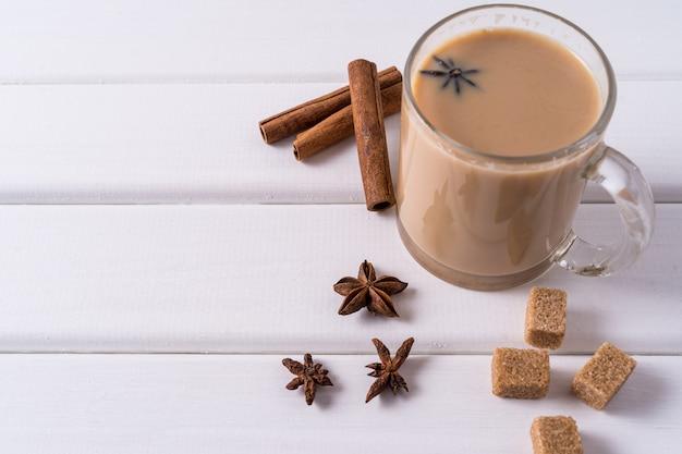 Masala chai thee in een mok, bruine suiker, kaneelstokjes en anijs over witte tafel.