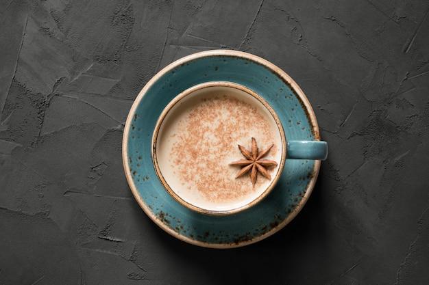 Masala indische thee of koffie in blauwe kop met kruiden en kaneel op zwarte. bovenaanzicht