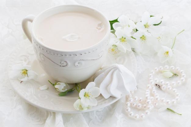 Masala thee chai latte zelfgemaakte traditionele indiase zoete melk met kruiden drank in porseleinen kopje op houten tafel muur