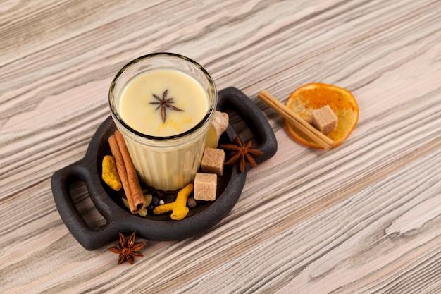Masala-thee in een glazen beker op een houten tafel, bovenaanzicht. originele portie op een houten bord met suiker, kruiden en gedroogde sinaasappel. detailopname.