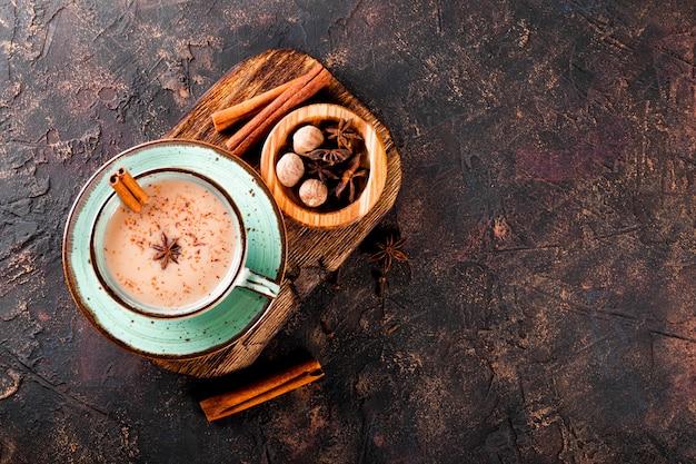 Masala thee indiase traditionele thee met melk en kruiden in een kopje op de donkere achtergrond bovenaanzicht gratis