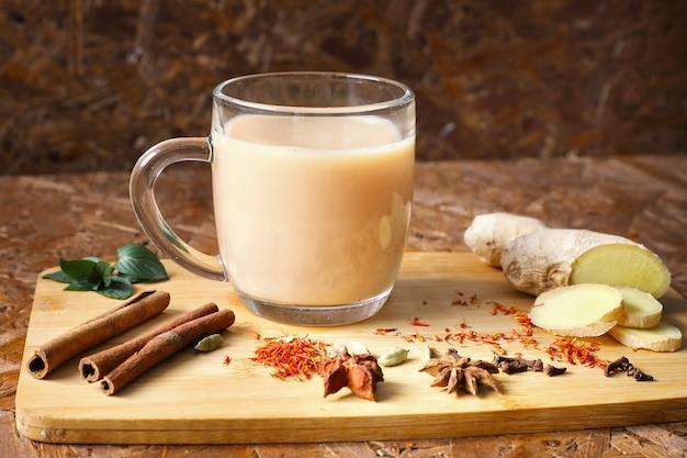 Masala-thee. verkwikkende thee met kruiden, ingrediënten op het bord. donkere textuur achtergrond.