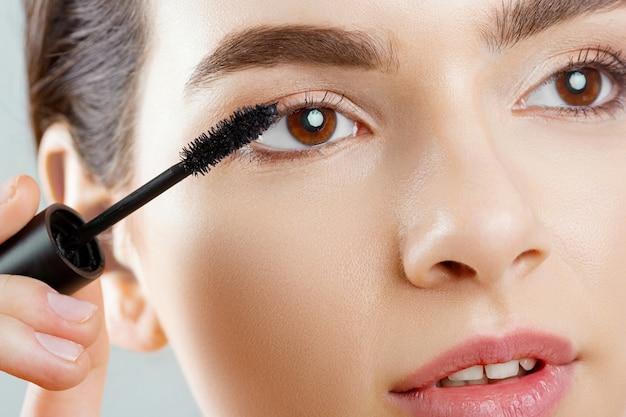 Mascara close-up van een mooie jonge vrouw een gezicht met een schoonheid make-up, frisse zachte huid mascara met cosmetische borstel aanbrengen.