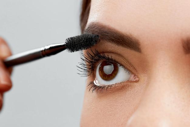 Mascara. close-up van mooie jonge vrouw gezicht met schoonheid make-up, frisse, zachte huid en lange zwarte dikke wimpers mascara met cosmetische borstel toe te passen.