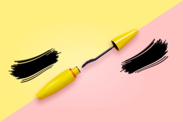 Mascara in gele buis met open penseel op roze en gele zonnebril met nepwimpers.
