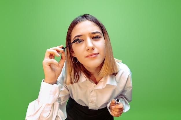 Mascara. meisje droomt van beroep van visagist. jeugd, planning, onderwijs en droomconcept. wil een succesvolle werknemer worden in de mode- en stijlindustrie, kapselartiest.