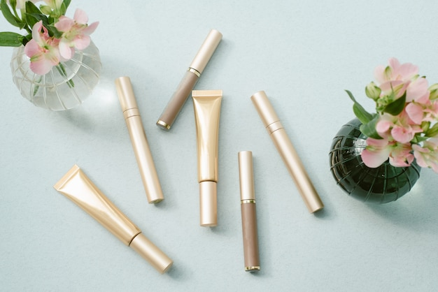 Mascara's in verschillende gouden pakketten naast een vaas met bloemen. het concept van make-up, mode en schoonheid