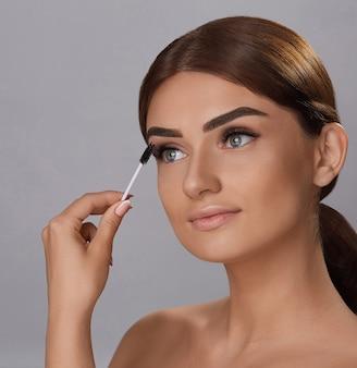 Mascara. schoonheid make-up, frisse zachte huid en lange zwarte dikke wimpers mascara aanbrengen met cosmetische borstel. wimpers extensions. valse wimpers.