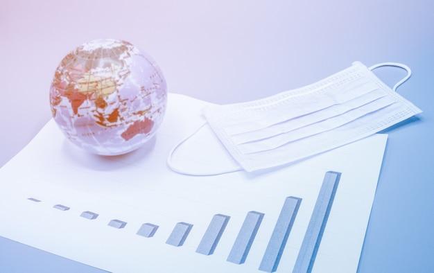 Masker en de aardbol op de grafiek die het toenemende aantal geïnfecteerde patiënten van over de hele wereld tijdens crisis covid-19 laat zien. business, economie, gezondheidszorg concept