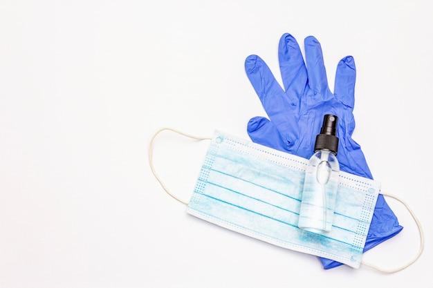 Masker, handschoenen, ontsmettingsmiddel dat op witte achtergrond wordt geïsoleerd