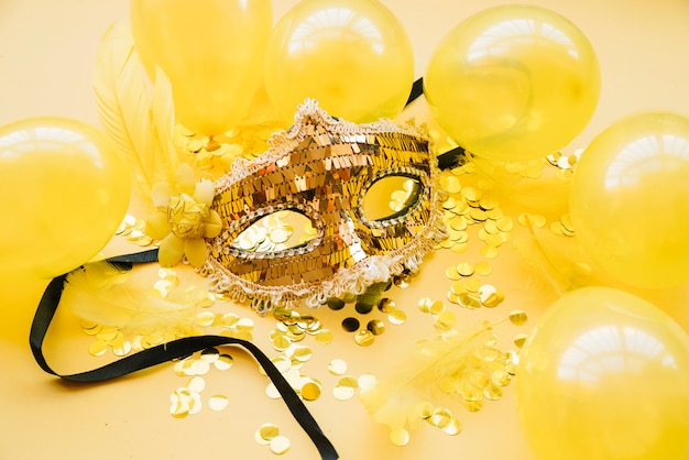 Masker in de buurt van ballonnen en confetti