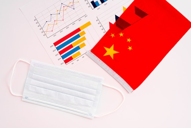 Masker om besmettingen en chinese vlag te vermijden die op witte achtergrond wordt geïsoleerd.