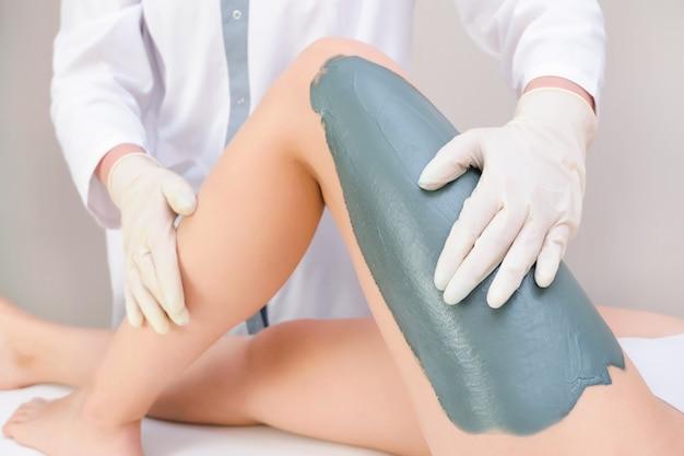 Masker op het been, been huidverzorging, jonge vrouw bij de receptie bij de schoonheidsspecialiste. peeling been